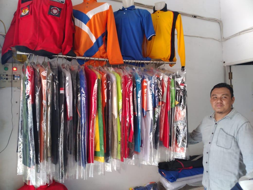 Nurdiansyah, Pemiliki Dian Jaya Konveksi Sedang Menunjukkan Berbagai Pilihan Baju OLah Raga